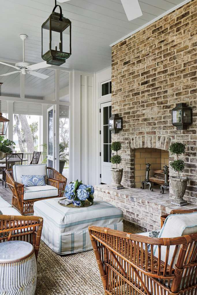 Outdoor screened living space with brick fireplace with mixed blue and white outdoor furniture