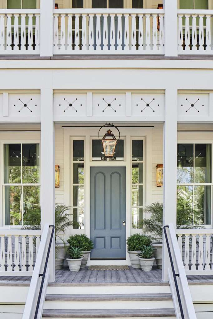 Blue gray front door flanked by sconces, hanging lantern, and planters with ferns