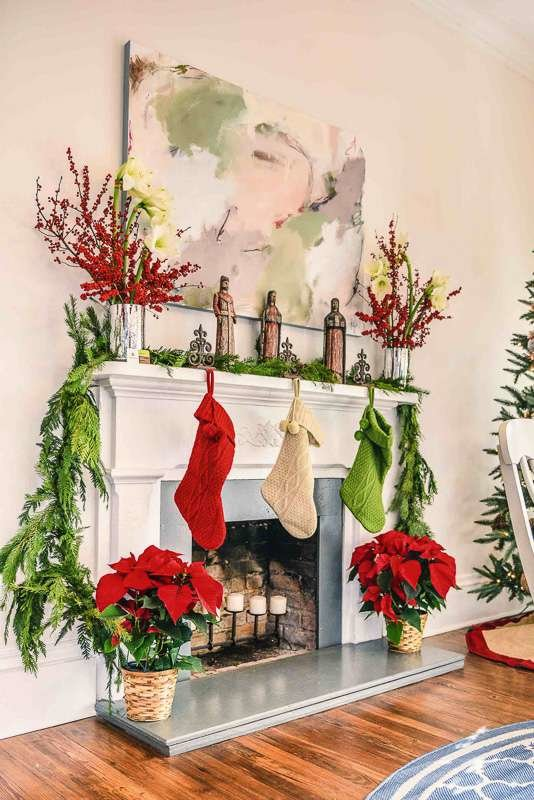 Traditional white painted fireplace with red and apple green stockings and poinsettia plants