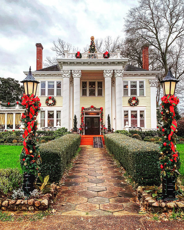 Georgia mansion decorated for Christmas.  Red bows, garland wrapped columns and rooftop Christmas Tree!