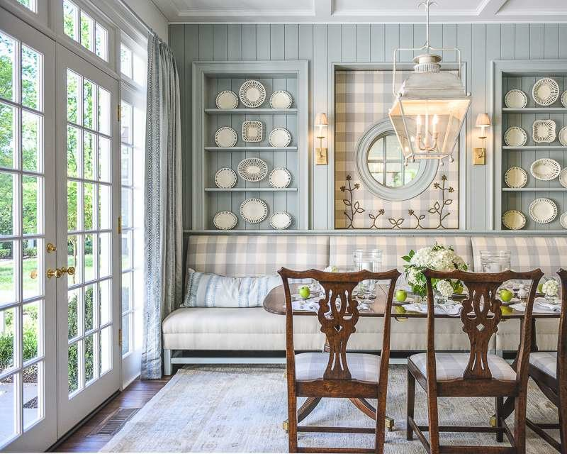 Breakfast room with traditional dining table and chairs, lantern style chandelier, blue checked fabric  on built in bench