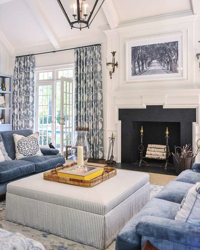 Family room in shades of blue and white, striped ottoman , blue velvet sofas