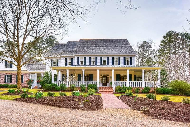 Milton GA farmhouse painted white with wrap around front porch, brick sidewalk and pea gravel driveway
