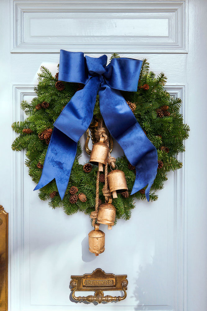 A gorgeous front door christmas wreath decorated with blue ribbon and rustic bells by Southern Living Magazine