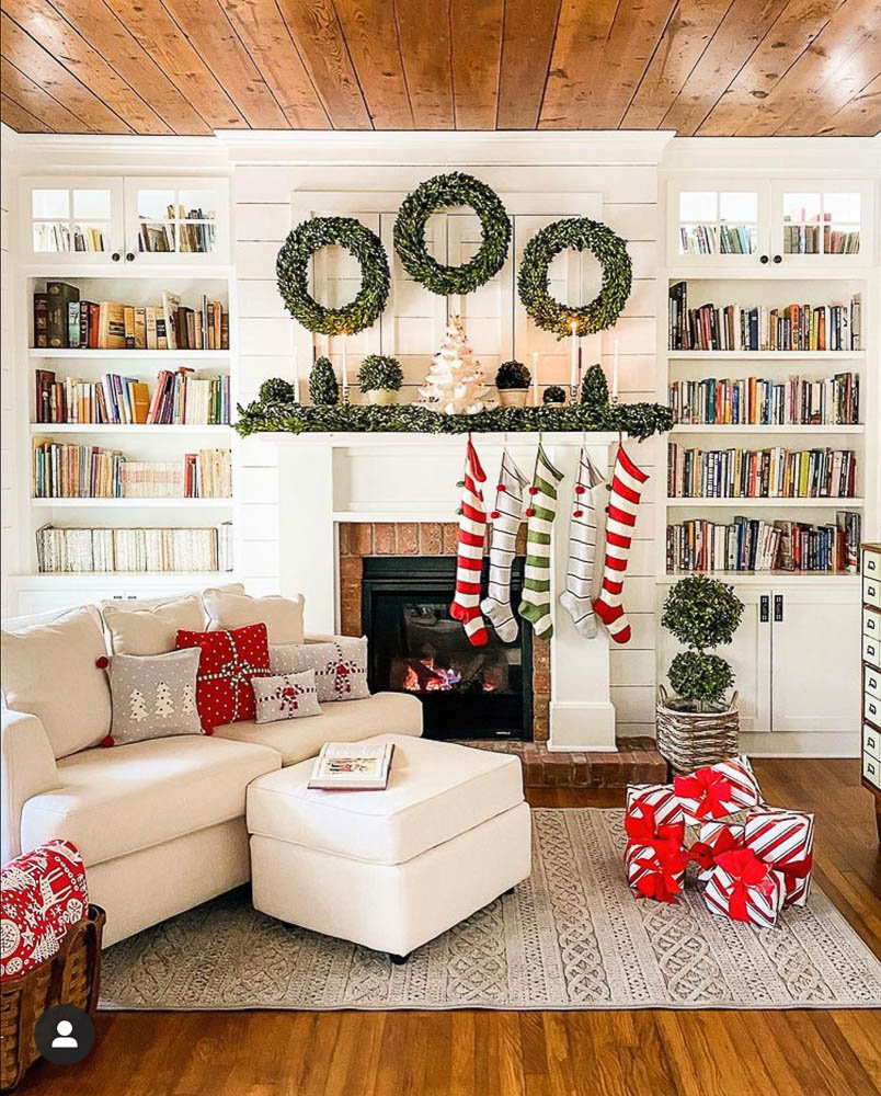 A living room decorated for the holidays by Simply Southern Cottage featuring a large book case and bookshelves