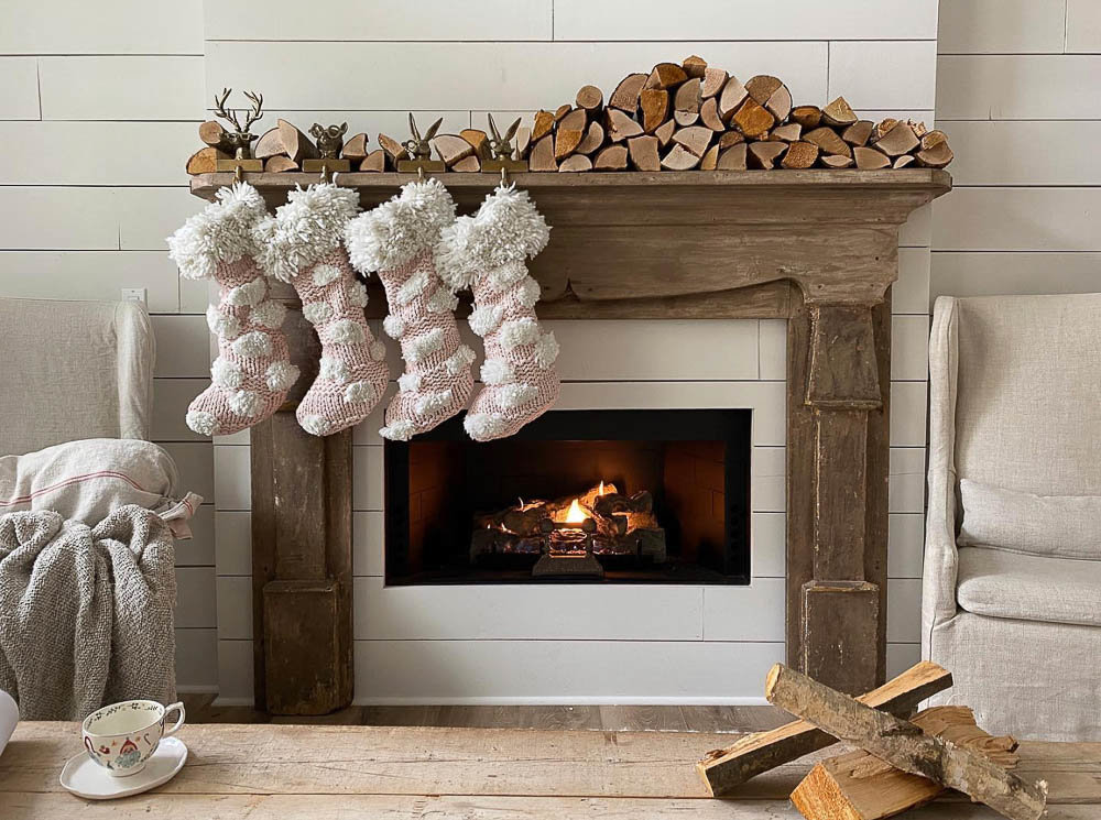 A woodsy and rustic Christmas decor themed mantel and fireplace featuring firewood and cozy neutrals by With Love Dani