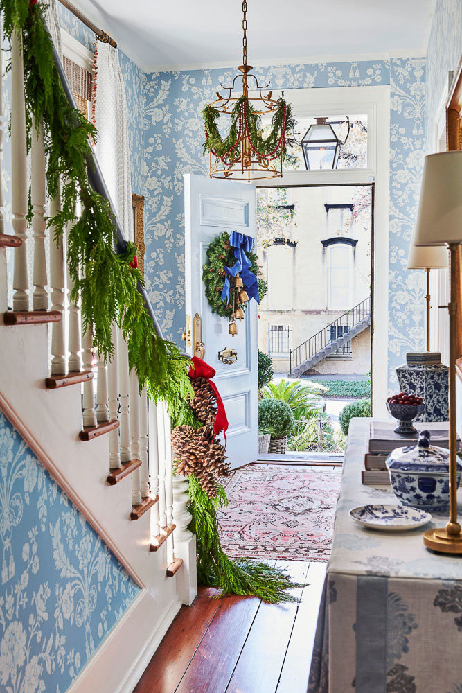 Garland lining the staircase and chandelier for Christmas | Christmas decor inspiration and Southern Living Mag holiday edition