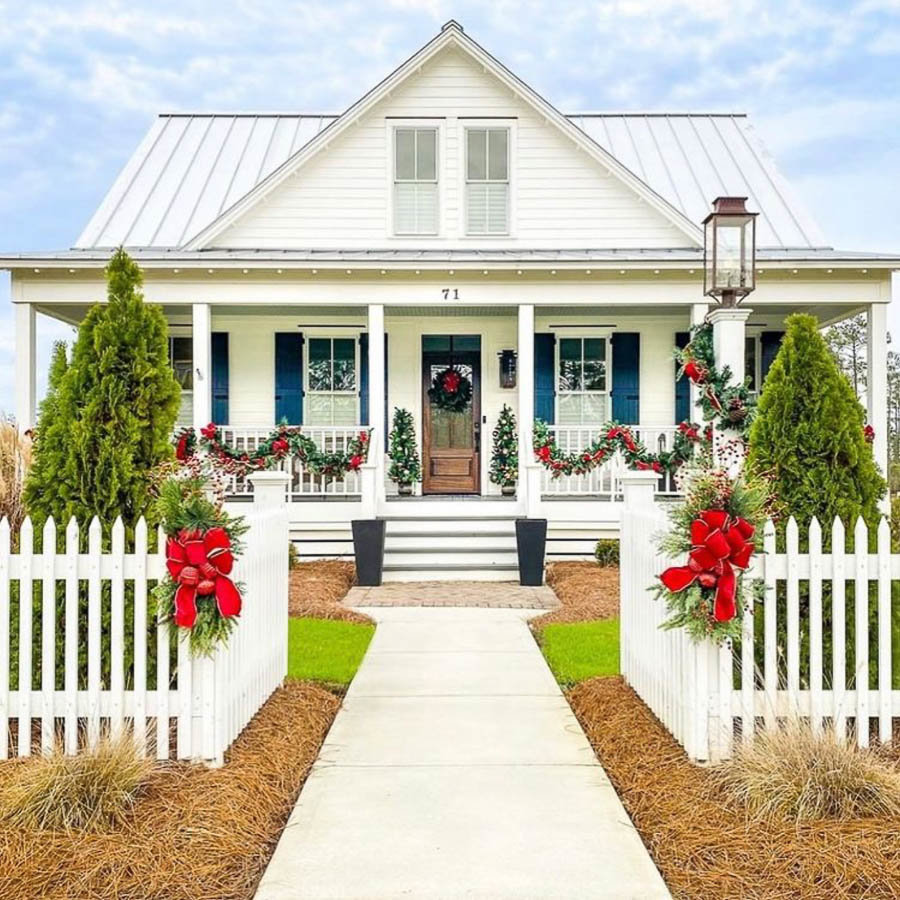 A beautiful wrap around porch decorated for Christmastime by Simply Southern Cottage
