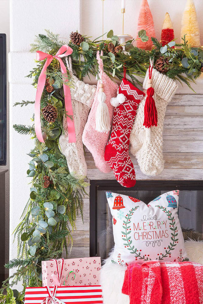 A red and white Christmas decor themed mantel and fireplace featuring stockings and wrapped gifts | American Farmhouse Style