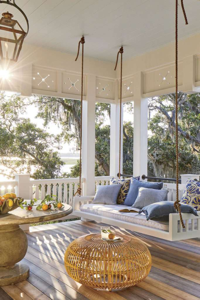 Porch painted white with eclectic mix of furniture, porch swing piled with a mix of blue patterned pillows