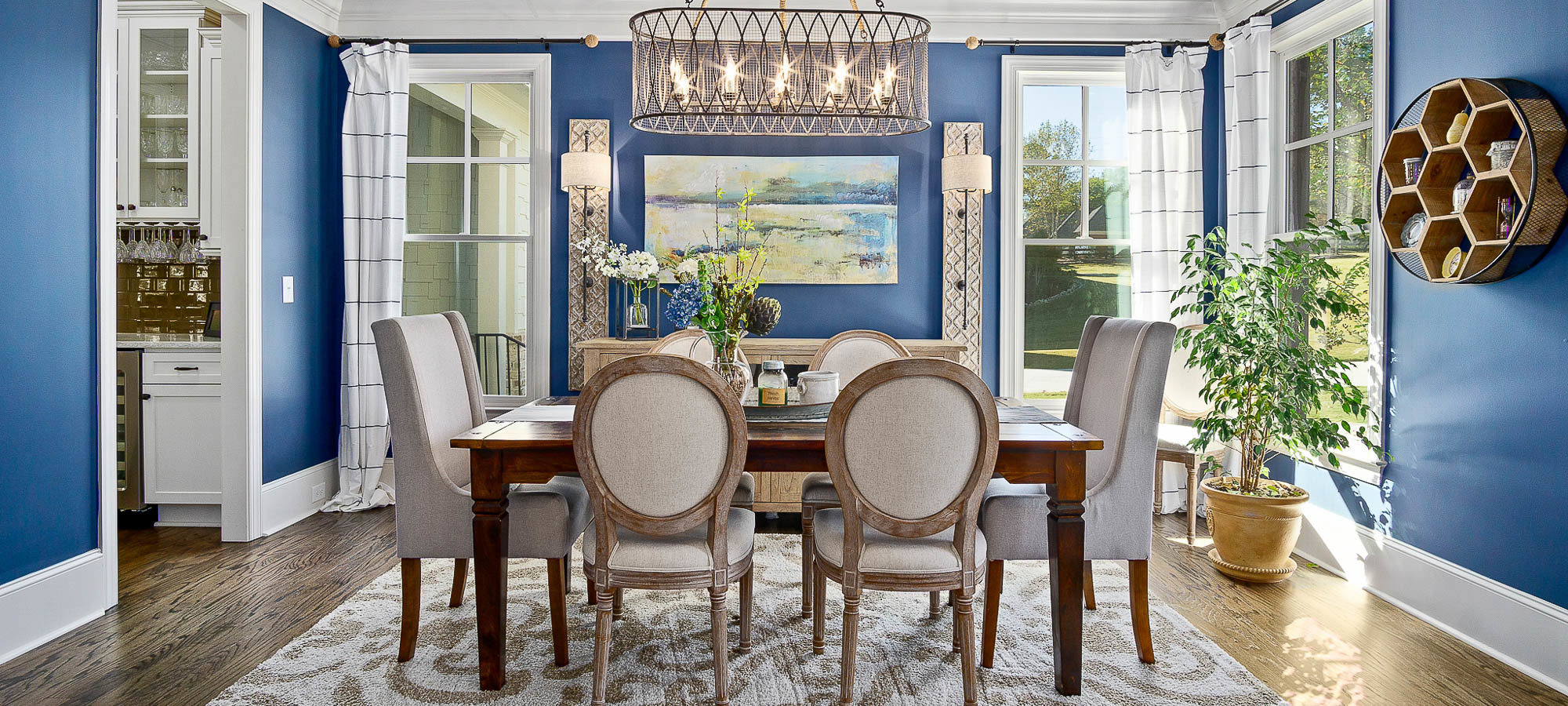 Traditional style dining room with bold blue painted walls, white trim and hardwood floors