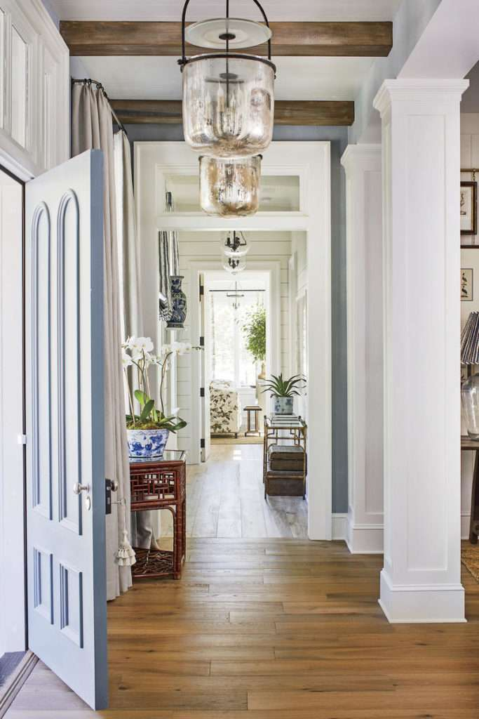 Foyer entry featuring bell jar lanterns, white beamed ceiling with wood planks